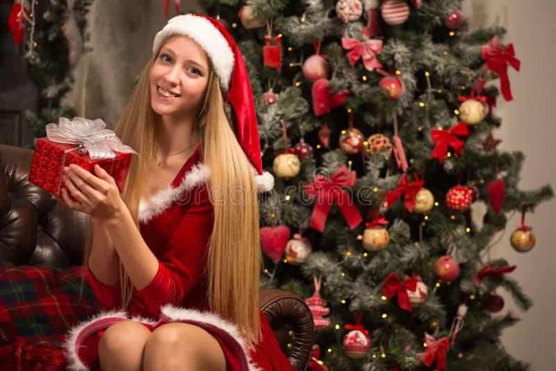 Het mooie model kleedde zich als Kerstman met dichtbij een Kerstboom royalty-vrije stock fotografie