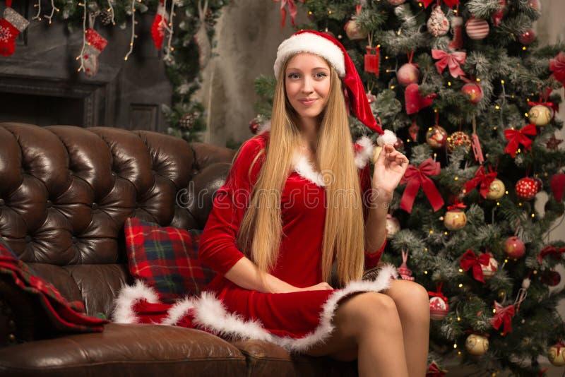 Het mooie model kleedde zich als Kerstman met dichtbij een Kerstboom stock afbeelding