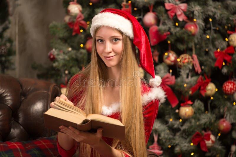 Het mooie model kleedde zich als Kerstman met dichtbij een Kerstboom royalty-vrije stock afbeeldingen