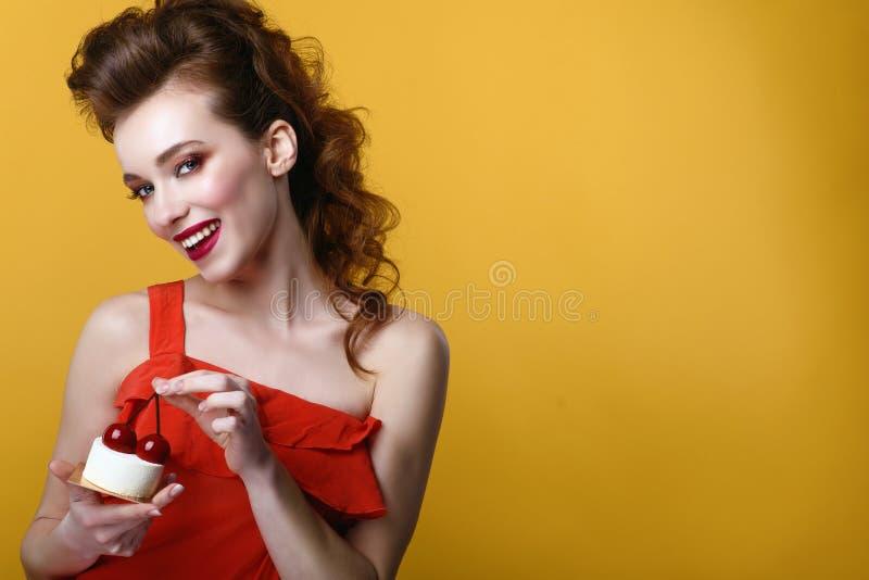 Het mooie model met creatief kapsel en kleurrijk maakt omhoog het houden van smakelijk die gebakje met kersen op de bovenkant wor stock afbeelding