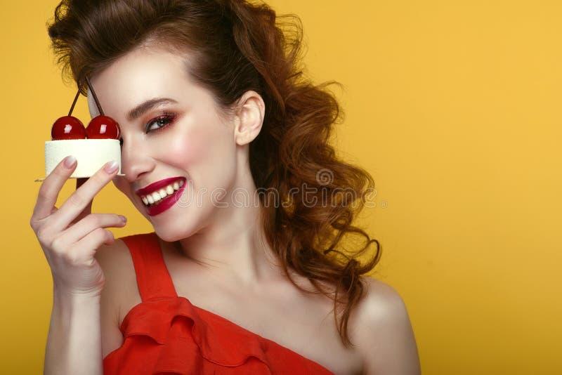 Het mooie model met creatief kapsel en kleurrijk maakt omhoog het houden van smakelijk die gebakje met kersen voor haar oog wordt royalty-vrije stock afbeelding