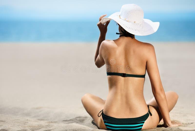Het mooie model ontspannen op een strand stock afbeeldingen