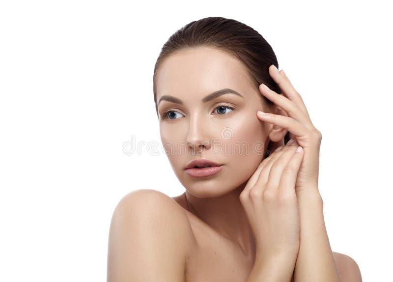 Het mooie model stellen met naakte schouders wat betreft haar gezicht royalty-vrije stock foto's