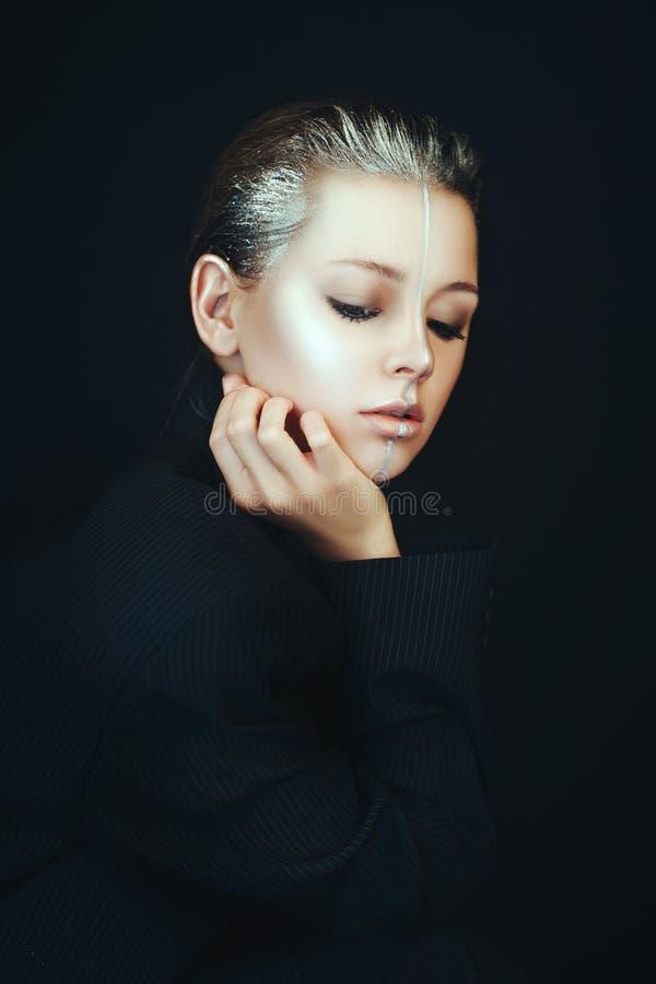 Het mooie model stelt in een badkamers met creatieve zilveren make-up stock afbeelding