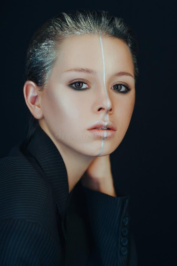 Het mooie model stelt in een badkamers met creatieve zilveren make-up royalty-vrije stock afbeeldingen