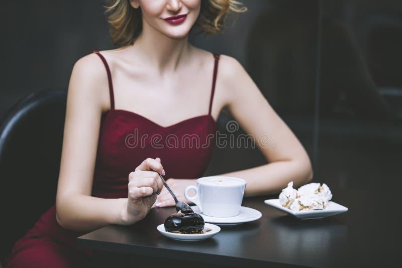 Het mooie model van het vrouwenblonde in een rode jumpsuit elegant met Cu stock fotografie