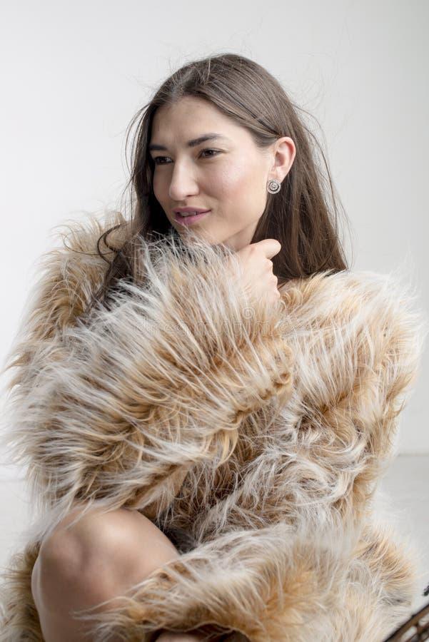 Het mooie modelbrunette van het vrouwenmeisje in een bontjas royalty-vrije stock foto's