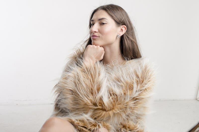 Het mooie modelbrunette van het vrouwenmeisje in een bontjas royalty-vrije stock fotografie