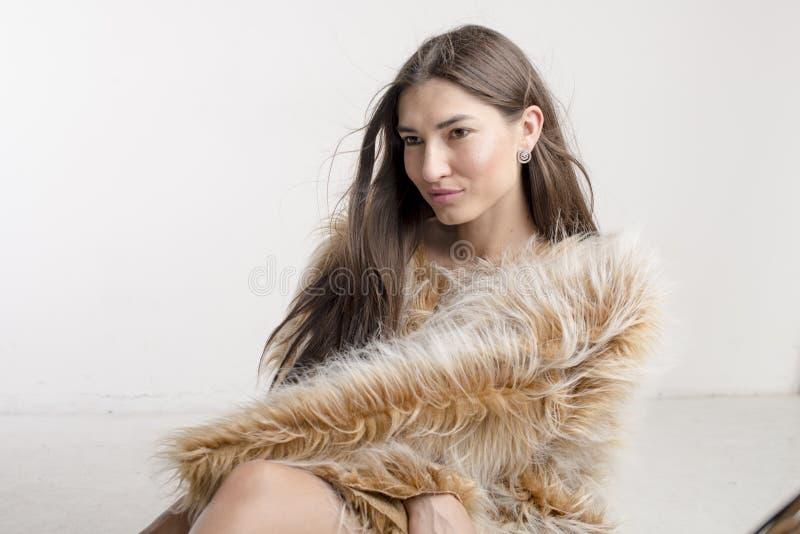 Het mooie modelbrunette van het vrouwenmeisje in een bontjas royalty-vrije stock afbeeldingen