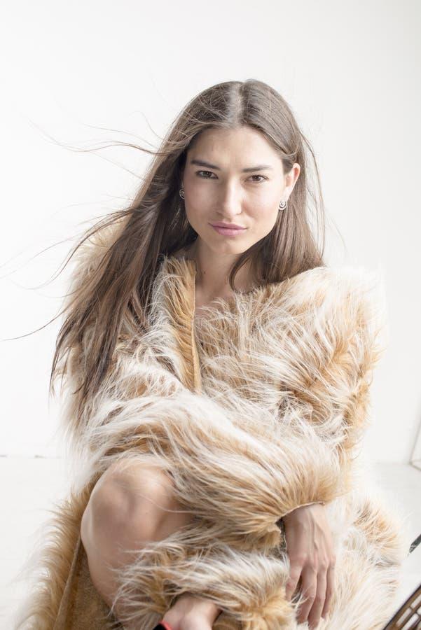 Het mooie modelbrunette van het vrouwenmeisje in een bontjas stock foto's