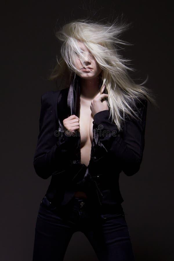 Het mooie modieuze en sexy half-naked blondemeisje in zwart kostuum stelt bij donkere achtergrond royalty-vrije stock fotografie
