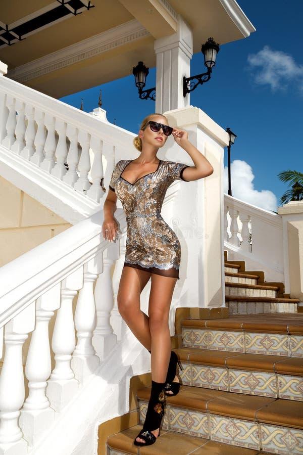 Het mooie modieuze jonge vrouw stellen in het park, zonnebril, seqines kleedt zich, hoge hielen, blondehaar De foto van de manier stock afbeeldingen