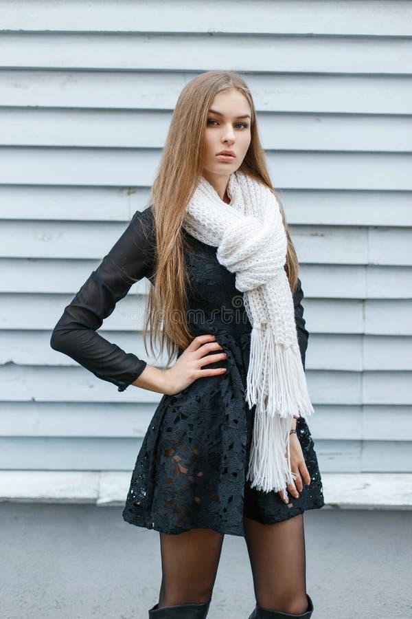 Het mooie modieuze meisje in een gebreide sjaal en een zwarte kleden zich op t royalty-vrije stock fotografie
