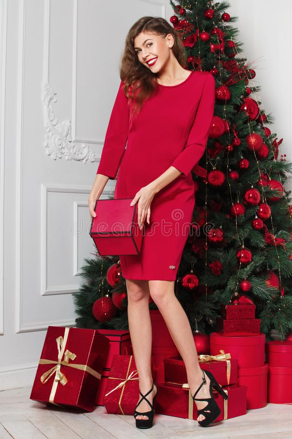 Het mooie modieuze meisje gekleed in rode kleding stelt met rode doos in haar handen naast de Nieuwjaarboom royalty-vrije stock foto