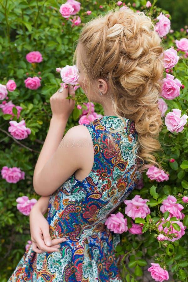 Het mooie mooie zachte sexy meisje die dichtbij nam struiken in de de zomer warme dag met mooi haar bloeien toe stock afbeelding