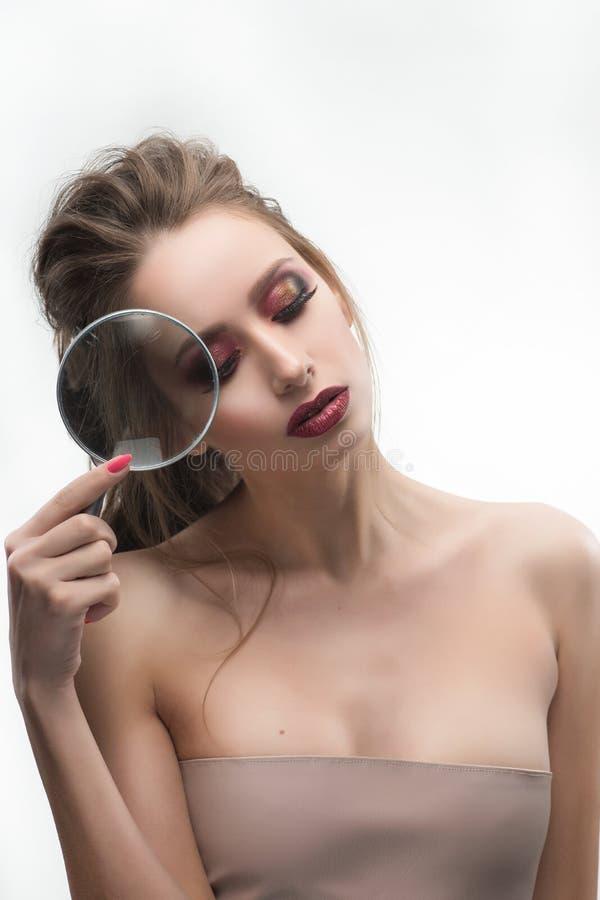 Het mooie naakte schoudersmeisje toont vergroot met een magnifyi stock foto's