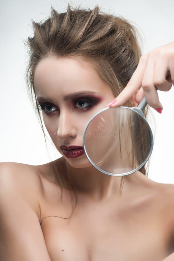 Het mooie naakte schoudersmeisje toont vergroot met een magnifyi stock afbeeldingen