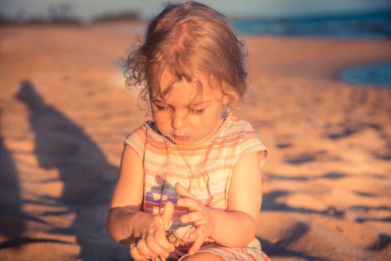 Het mooie nieuwsgierige de peuter van het kindmeisje spelen op strand met kluizenaarkrab tijdens de levensstijl van het concepten royalty-vrije stock fotografie