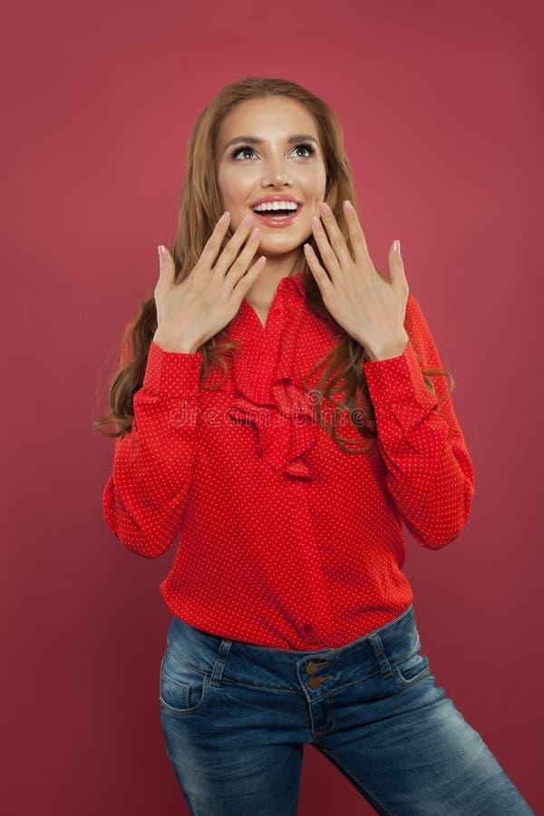 Het mooie opgewekte verraste portret van het studentenmeisje Gelukkige jonge vrouw met geopende mond op kleurrijke heldere roze a stock afbeelding
