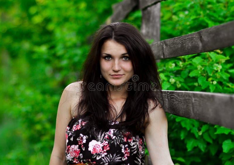 Het mooie overweldigen, uitstekend, leuk meisje met perfect gezicht, donkerbruin meisje met donkere haartribune dichtbij houten o royalty-vrije stock afbeeldingen