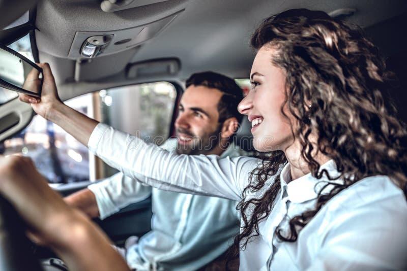 Het mooie paar bekijkt achteruitkijkspiegel en glimlacht terwijl het zitten in hun nieuwe auto royalty-vrije stock afbeelding