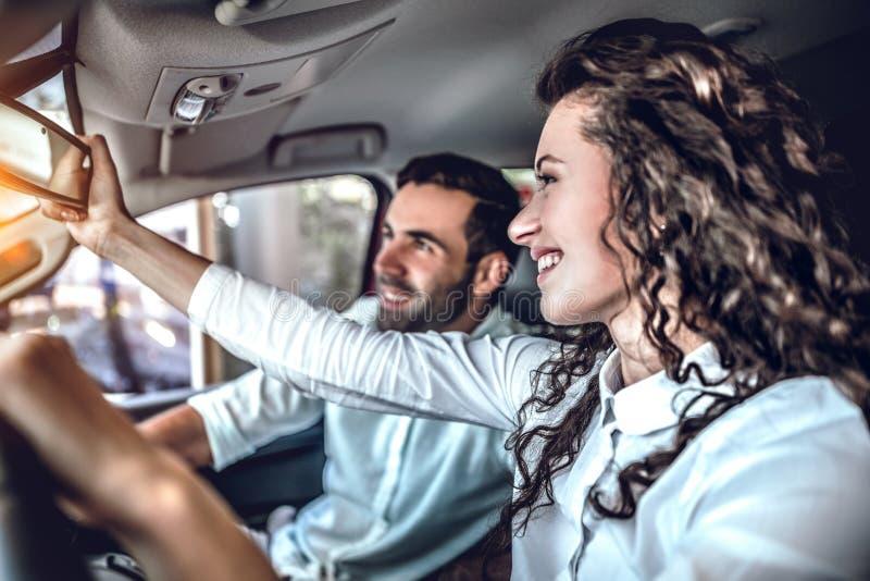 Het mooie paar bekijkt achteruitkijkspiegel en glimlacht terwijl het zitten in hun nieuwe auto stock foto