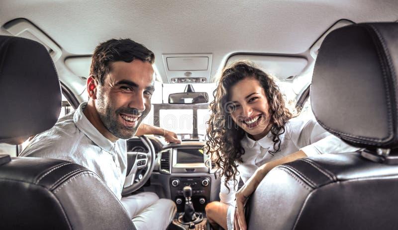 Het mooie paar bekijkt camera en glimlacht terwijl het zitten in hun nieuwe auto stock afbeeldingen