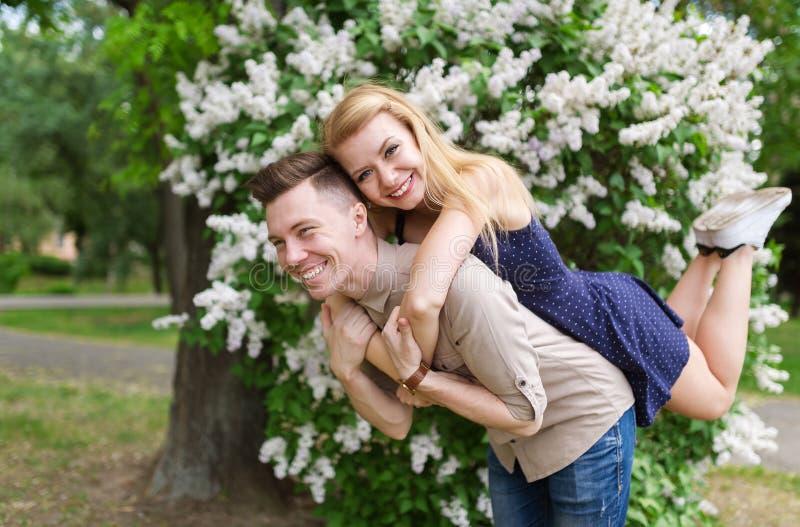 Het mooie paar brengt volkomen tijd in het stadspark door Het mooie paar is op de achtergrond van de kersenbloesems royalty-vrije stock afbeelding