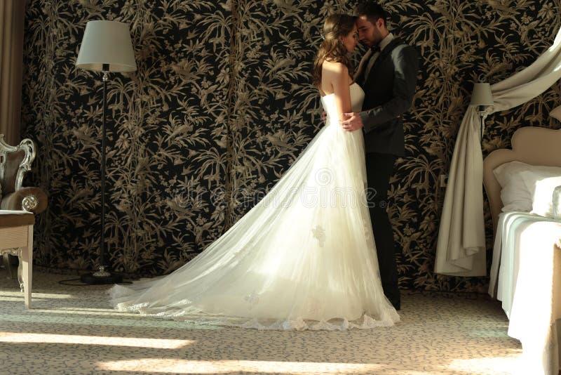 Het mooie paar, de bruidegom en de bruid dragen huwelijkskleren, omhelzend in slaapkamer stock foto