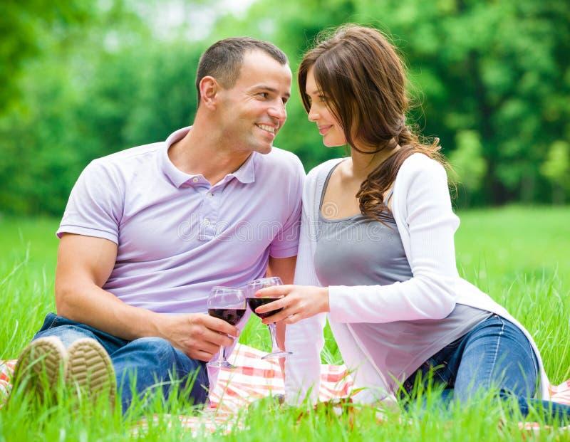 Het mooie paar drinkt wijn in park royalty-vrije stock fotografie