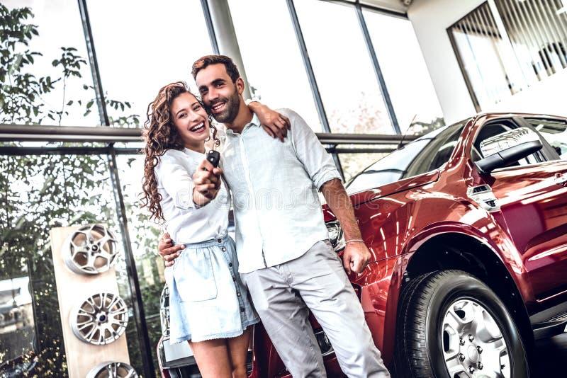 Het mooie paar houdt een sleutel van hun nieuwe auto, het bekijken camera en het glimlachen stock foto's