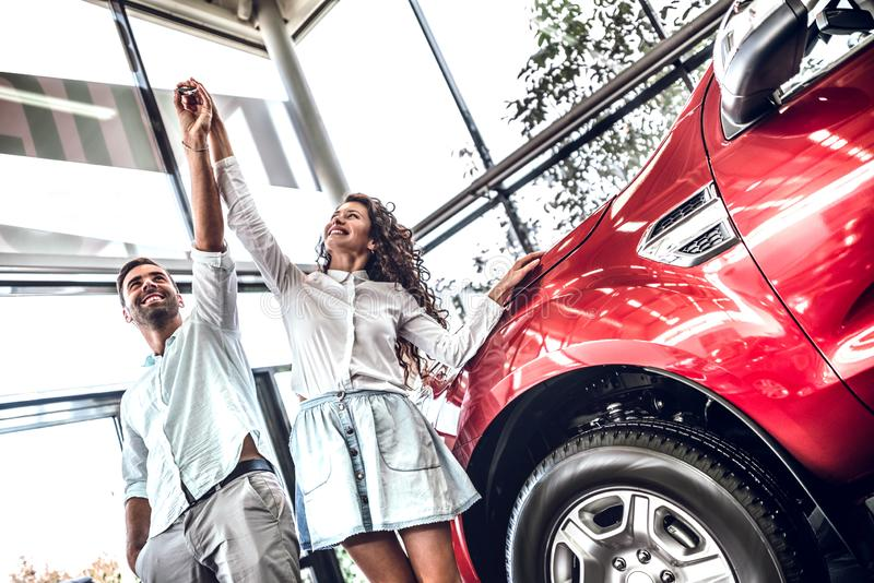 Het mooie paar houdt een sleutel van hun nieuwe auto, het kijken in de sleutel en het glimlachen royalty-vrije stock afbeelding