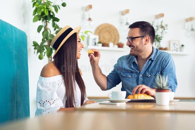 Het mooie paar in liefde zit in koffie De jonge man voedt zijn vrouw en het glimlachen stock fotografie