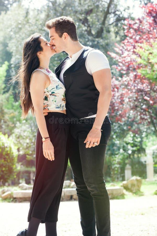 Het mooie paar omhelst en kust Het houden van verhouding en het voelen outdoors royalty-vrije stock fotografie