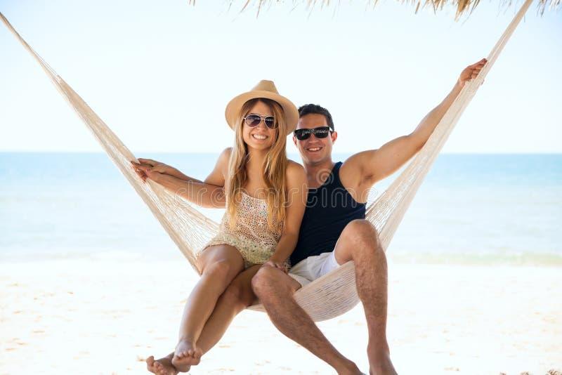 Het mooie paar ontspannen in een hangmat royalty-vrije stock afbeelding