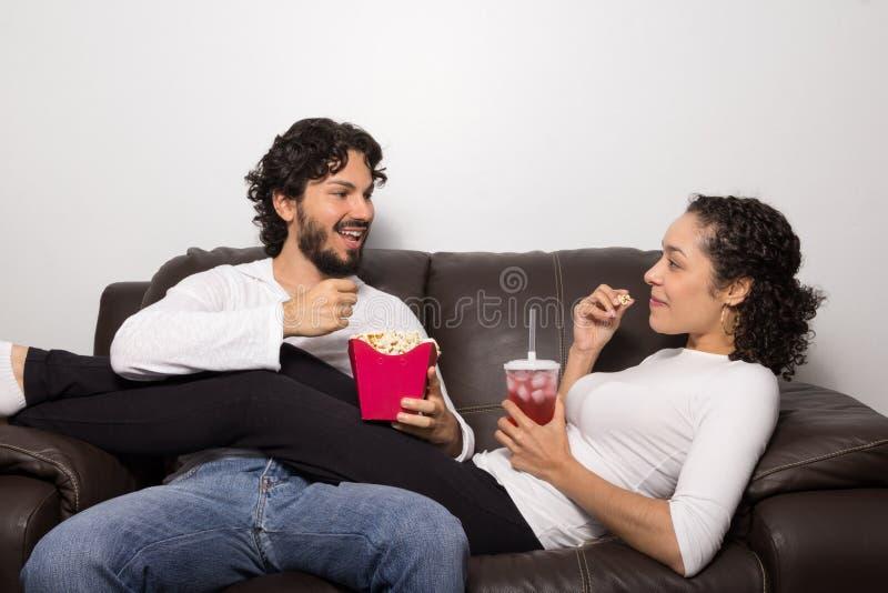 Het mooie paar spreekt op de laag Het eten van Popcorn Relaxi royalty-vrije stock fotografie