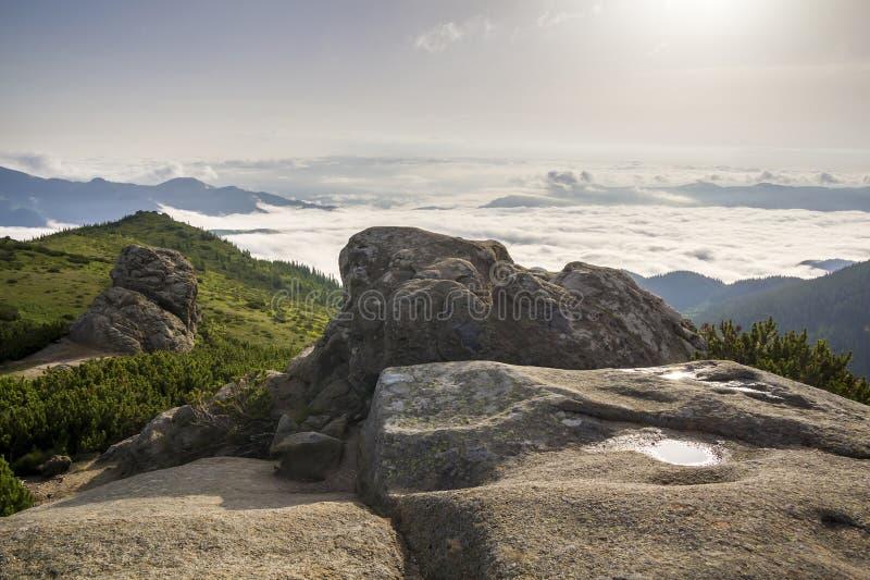 Het mooie panorama van de de zomerberg bij dageraad Reusachtige kei met de vulklei van het regenwater op groene rotsachtige bergb royalty-vrije stock foto's