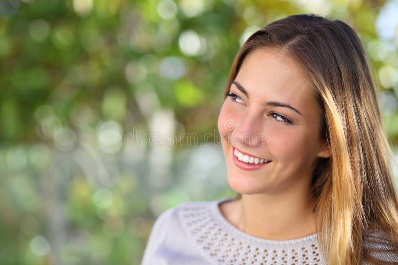 Het mooie peinzende vrouw glimlachen die boven openlucht kijken royalty-vrije stock fotografie