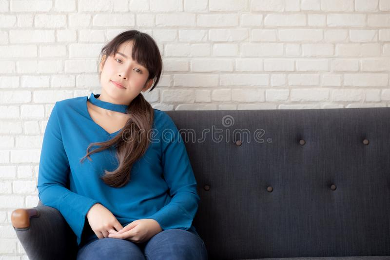 Het mooie portret jonge Aziatische vrouw gelukkige zitting en glimlachen en het bekijken camera op bank met toevallig woonkamer stock afbeeldingen