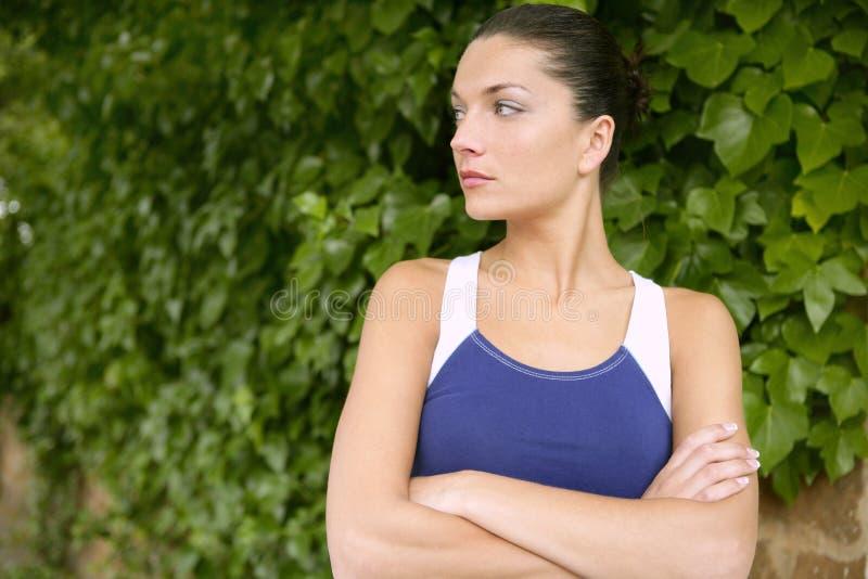 Het mooie portret van de sportvrouw over groene bladeren royalty-vrije stock fotografie