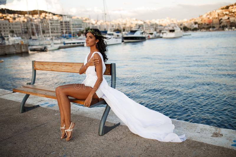 Het mooie portret van een donkerbruine jonge vrouw stelt sensueel in witte kleding op bank, achter Middellandse Zee in Griekenlan stock afbeelding