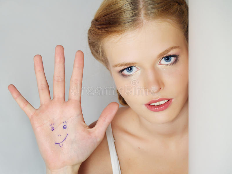 Het mooie positieve meisje toont een palm met tekening royalty-vrije stock afbeelding
