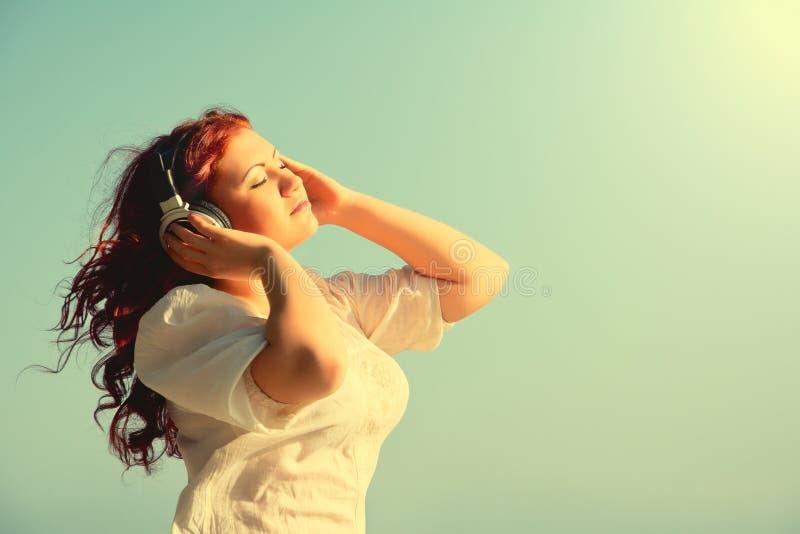 Het mooie redhead meisje geniet van muziek, headphon stock afbeelding
