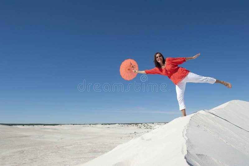 Het mooie rijpe vrouw in evenwicht brengen op zandduin royalty-vrije stock foto