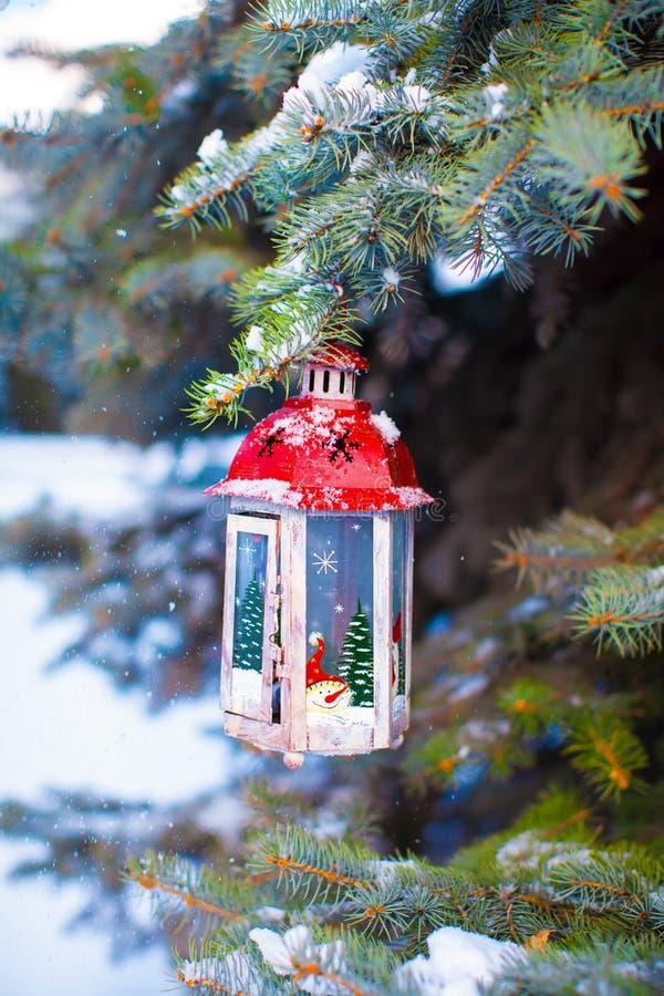 Het mooie rode fairytalelantaarn hangen op sneeuwspartak in bos stock afbeelding
