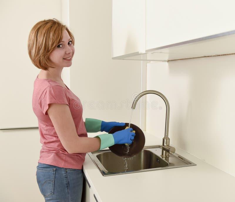 Het mooie rode haarvrouw gelukkig glimlachen en positief die de schotels wassen bij keukengootsteen royalty-vrije stock foto