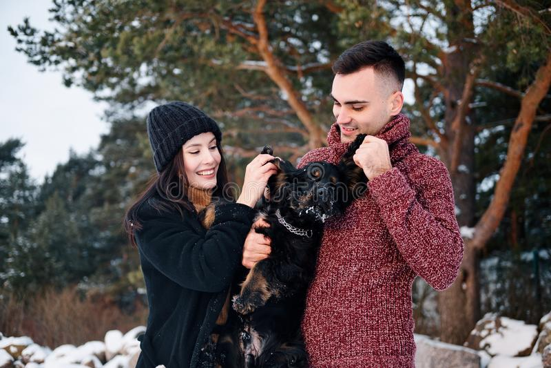 Het mooie romantische paar heeft in openlucht pret met hun hond in de winterdag stock afbeelding