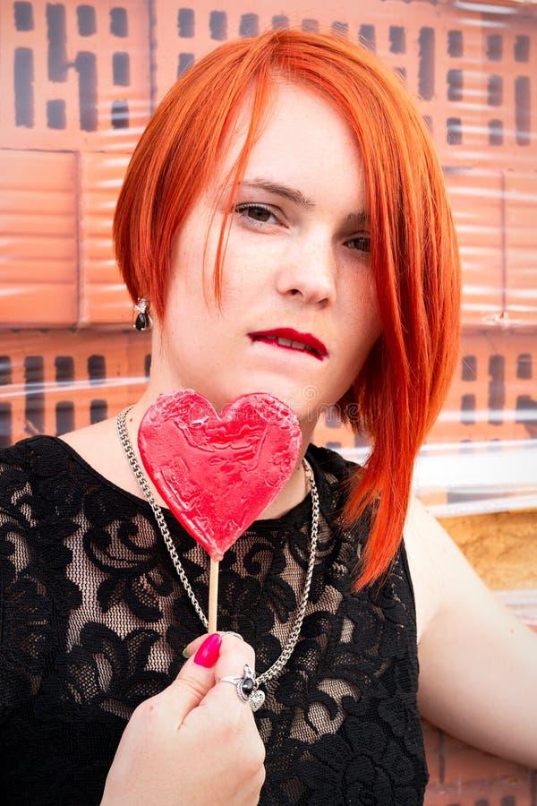 Het mooie roodharige meisje bijt haar lip met suikergoed in de vorm royalty-vrije stock foto's