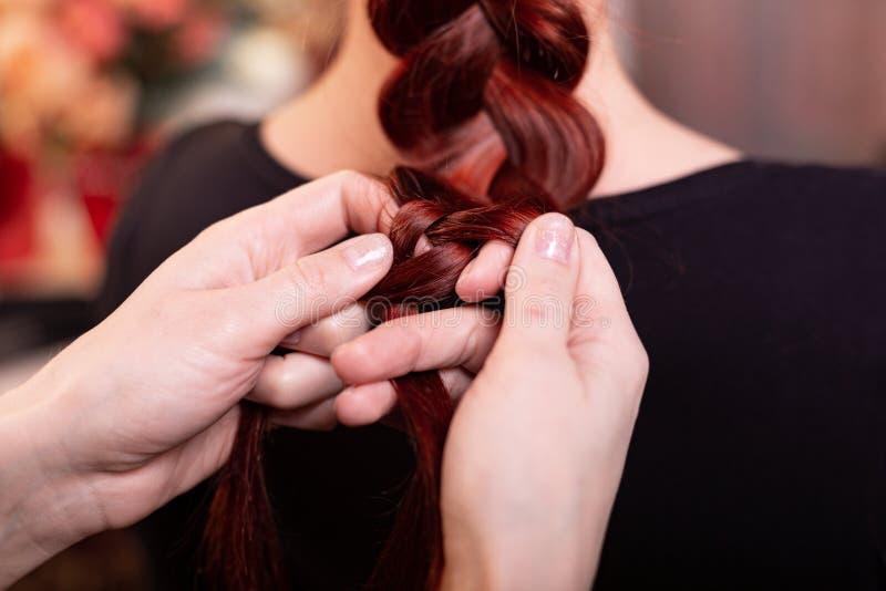 Het mooie, roodharige meisje met lang haar, kapper weeft een Franse vlecht, in een schoonheidssalon Professionele haarverzorging royalty-vrije stock afbeeldingen