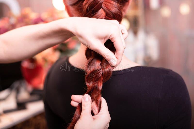 Het mooie, roodharige meisje met lang haar, kapper weeft een Franse vlecht, in een schoonheidssalon Professionele haarverzorging stock foto